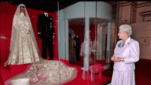 Queen Elizabeth looks at her brocade wedding dress at the Museum of London